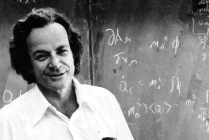 Richard Feynman (inspiratiebron van Bord&Stift) in een witte blouse, voor een zwart krijtbord met formules erop