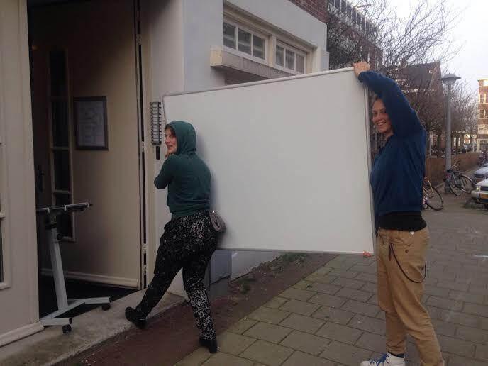Verhuizing van Bord&Stift. Violet en Rosalie tillen een whiteboard het nieuwe kantoor binnen.