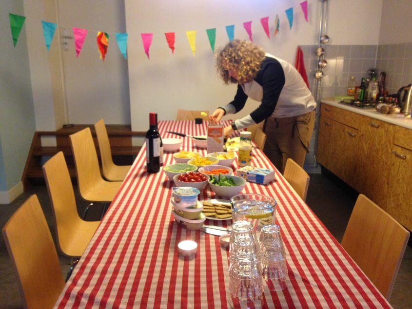 De feestelijke borrel van Bord&Stift ter opening van het nieuwe kantoor. Een tafel met rood-wit geblokt kleed met hapjes erop. Slingers hangen aan het plafond en Violet maakt de hapjes klaar.