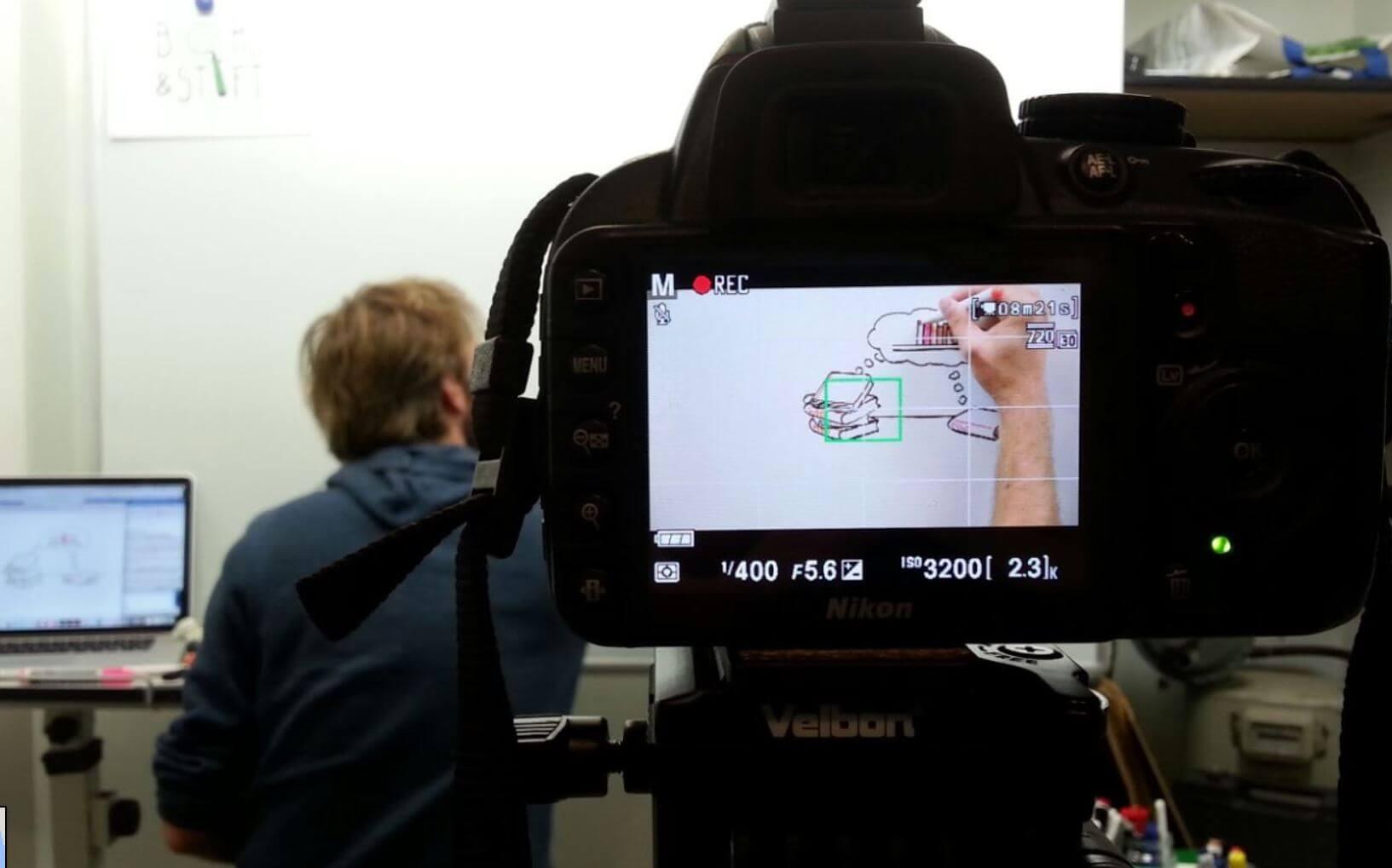 Nicky tekent een filmpje op een whiteboard, de camera is groot in beeld en daarin zie je hoe hij het filmpje tekent