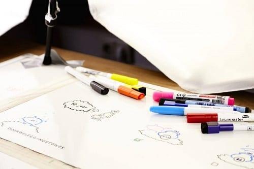 Een ingezoomde foto van een whiteboard die op een tafel ligt wordt belicht door studiolampen. Op het whiteboard liggen blauwe, rode, gele, zwarte, oranje en roze stiften.