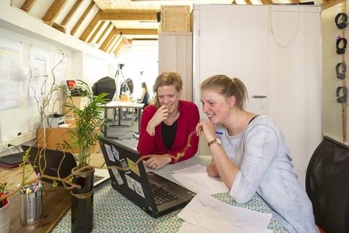 Een ruimte met twee tegen elkaar geschoven tafels. Twee laptops staan op de tafels en twee vrouwen kijken lachend naar één van de laptopschermen.