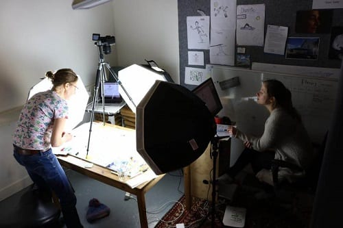 In een kamer staat een bureau waar een whiteboard, een camera en drie grote lampen op staan. Één vrouw tekent op het whiteboard terwijl een andere vrouw de beelden op een laptop naast te tafel bekijkt.