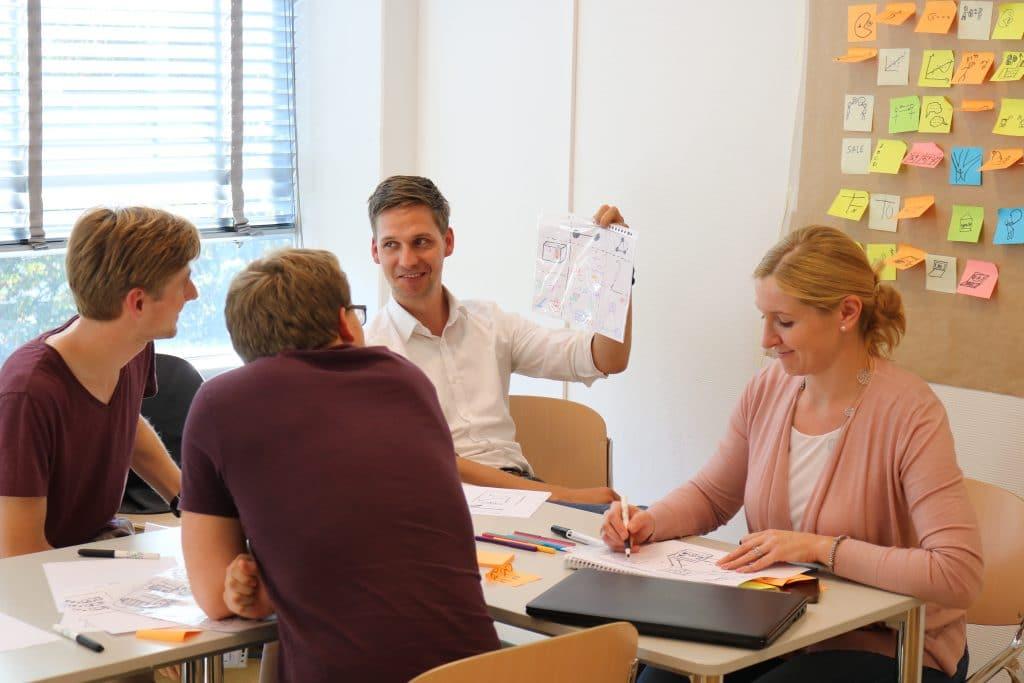 Man houdt papier met tekening omhoog tijdens vergadering met drie anderen