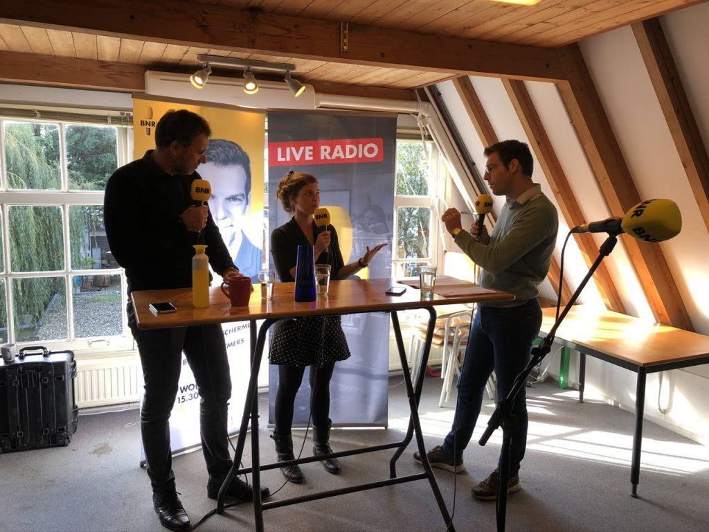 vrouw tussen twee lange mannen in radio-interview